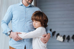 Nice pleasant boy closing his eyes. Together with the father. Nice pleasant cute boy closing his eyes and hugging his father while standing near him Stock Image