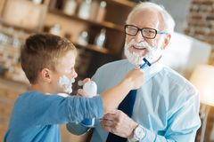 Nice pleasant boy shaving his grandfather. Useful skill. Nice pleasant positive boy looking at his grandfather and shaving him while learning to be a man Royalty Free Stock Photo