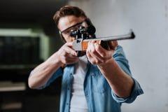 Nice pleasant man developing his shooting skills Royalty Free Stock Image