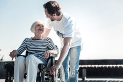 Nice pleasant man helping an elderly woman. Social worker. Nice positive pleasant men smiling and looking at the disabled elderly women while helping her Stock Images
