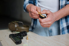 Nice pleasant man putting a bullet into the cartridge clip Royalty Free Stock Images