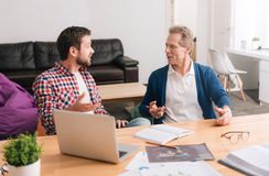 Nice pleasant men looking at each other. Heated discussion. Nice pleasant handsome men looking at each other and discussing a project while working together in stock photos