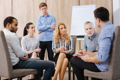 Nice pleasant people participating in the group discussion. Group of support. Nice pleasant friendly people sitting in the circle and sharing their problems stock photo