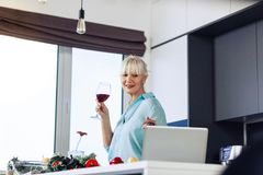 Nice pleasant woman standing in front of the laptop. Modern technology. Nice pleasant woman standing in front of the laptop while holding a glass of wine royalty free stock image