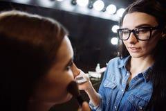 Nice pleasant woman using a makeup brush Stock Photo