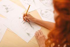 Girl with foxy hair drawing nice portrait. Nice portrait. Beautiful beaming girl with long curly foxy hair feeling inspired while drawing nice portrait Stock Photos