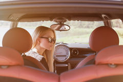 Nice portrait of blonde young woman. At the wheel of sport car with red interior, with sunglasses, natural makeup looking to the right Royalty Free Stock Images