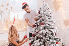Nice positive couple decorating the Christmas tree Stock Photo