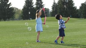 Joyful little asian kids playing with soap bubbles stock footage