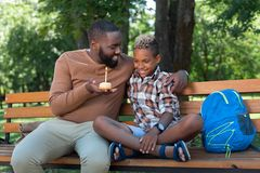 Nice positive man giving a cake to his son. From me. Nice positive men smiling to his son while giving him a cake stock images