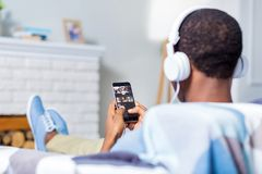 Nice positive man listening to a song. Favourite music. Nice positive cheerful man using his smartphone and listening to music in headphones while sitting on the Stock Images