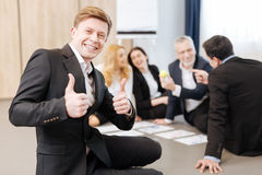Nice positive man showing OK sign. It is great. Nice positive delighted men showing OK sign and looking at you while feeling happy Royalty Free Stock Photography