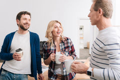 Nice positive people talking to each other. Warm atmosphere. Nice positive delighted people having drinks and talking to each other while being in the office Stock Photos