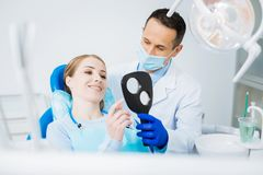 Nice positive woman looking at the result. After treatment. Nice positive young women holding a mirror and looking into it while assessing results of her dental Royalty Free Stock Photography
