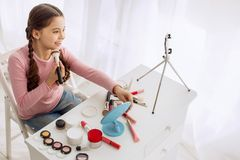 Nice pre-teen girl reviewing makeup products live. Wannabe makeup artist. Charming upbeat pre-teen girl posing for the camera and reviewing makeup products live Royalty Free Stock Images