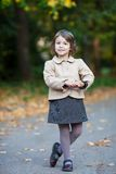 Nice preschooler girl in the autumn park. Small girl outdoor in the park with yellow leaves Royalty Free Stock Image