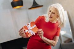 Joyful elderly woman holding a gift Stock Photos