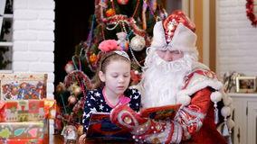 Nice pretty blonde girl with a pink bow in her hair, in a beautiful dress, is reading book with Santa Claus father stock video