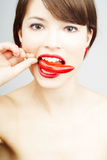 Nice pretty woman biting a chili pepper royalty free stock image