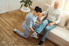 Nice professional caregiver holding her patients leg. Warming up muscles. Nice professional female caregiver holding her patients leg and moving it while warming stock images
