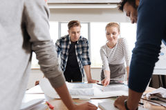Nice professional engineers focusing on their project. Important work. Nice professional delighted engineers standing at the table and looking at the drawings royalty free stock photography