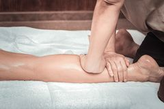 Nice professional skilled masseuse massaging female legs. Body massage. Nice professional masseuse massaging female legs while doing body massage royalty free stock image