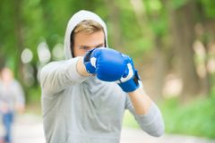 Nice punch. Boxing training endurance. Man athlete concentrated face with sport gloves practicing boxing nature. Background. Boxer ready to fight. Sportsman stock image