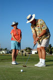 Nice putt. A senior man sinks a put while his partner watches royalty free stock images