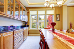 Nice red and brown dining room interior with wooden cabinets and Stock Photo