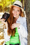 Nice red-haired girl photographer at work Stock Image