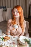Nice redhead woman eat breakfast in cafe. Portrait of young charming female drinking coffee and toasted sandwich in stock photo