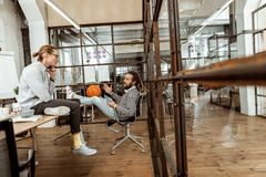 Nice relaxed young men having a conversation. Best friends. Nice relaxed men having a conversation while having a lunch at work stock photos