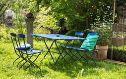 Nice relaxing place in the garden with blue furniture of wood. Royalty Free Stock Image