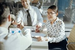 Cheerful colleagues submitting research results to their boss Royalty Free Stock Image