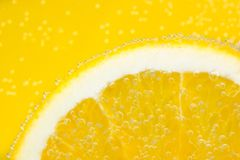 Nice ripe and juicy slice of an orange covered. With bubbles in soda water Royalty Free Stock Photography