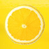 Nice ripe and juicy slice of an orange covered. With bubbles in soda water Royalty Free Stock Photo