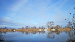 Nice river with smooth water surface and trees in frost. Beautiful Atmata river with smooth water surface, rainbow  and snowy trees in Rusne island, Lithuania Royalty Free Stock Photo