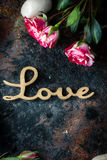 Nice roses and love message on rustic background Royalty Free Stock Image