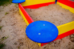 A nice sandbox playground filled . Surrounded by green grass,. Seen from top Stock Photo