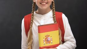 Nice schoolgirl holding vocabulary with Spanish flag, language studying, lessons. Stock footage stock footage