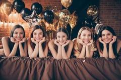 Nice-se charmiga gulliga söta attraktiva älskvärda olika gladlynta glade flickor som in ligger på festlig födelsedagdag för säng royaltyfria foton