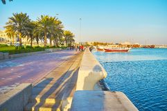 Coastal districts of Doha, Qatar. The nice seaside promenade with lush palms stretches along the shore of Persian Gulf, Doha, Qatar stock photography