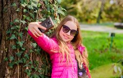 Nice selfie. little girl spend free time in park. happy child in park. summer. Natural beauty. Childhood happiness. make. Selfie on phone. Green environment royalty free stock image