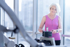 Nice senior lady standing near barbell at gym. Choosing weight. Pretty senior woman is standing at window in gym and choosing dumbbell for exercising Royalty Free Stock Photos