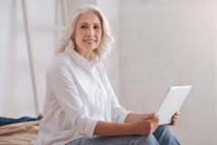 Nice senior woman holding a laptop. Modern device. Nice beautiful senior woman holding a laptop and smiling while sitting on the bed royalty free stock photos