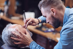 Nice serious barber shaving his client stock image