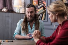 Nice serious fortune teller looking at the cards. I am ready. Nice serious fortune teller looking at the cards while being ready to put them on the table royalty free stock photo