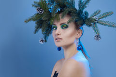 Nice serious woman with xmas tree-wreath on head looking at came Stock Images