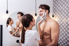 Husband with nice sexy abs hugging wife putting shaving foam. Nice sexy abs. Handsome husband with nice sexy abs hugging wife putting shaving foam on his face royalty free stock image