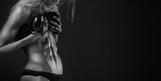 Nice sexy fitness woman showing abdominal muscles. Retouched isolated over black background Royalty Free Stock Image